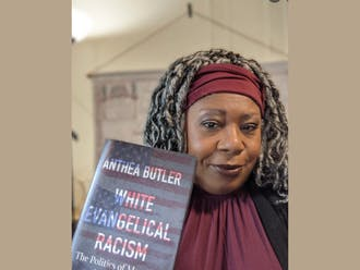 """Anthea Butler with her book, """"White Evangelical Racism: The Politics of Morality in America."""""""
