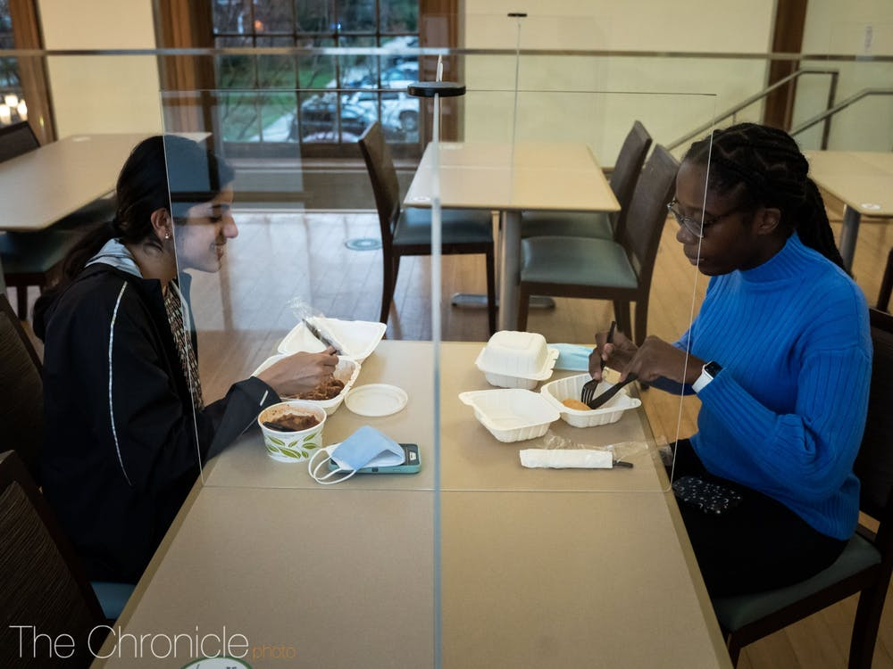 Freshmen Shanzeh Sheikh and Alaa Osman share dinner together at a table in Marketplace, separated by a plexiglass divider.
