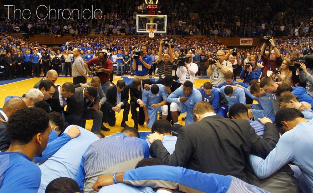 <p>Duke and North Carolina knelt at halfcourt before the Feb. 18 basketball game at Cameron Indoor Stadium to honor the late Tar Heel head coach Dean Smith.</p>