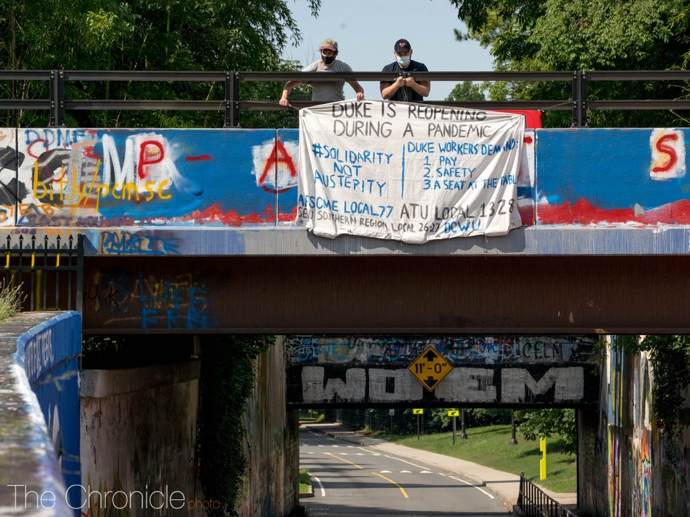 <p>Duke Graduate Student Union member Michael McGurk and co-chair Chris Huebner hang a banner over the East Campus bridge listing workers' demands for the reopening of Duke.&nbsp;</p>
