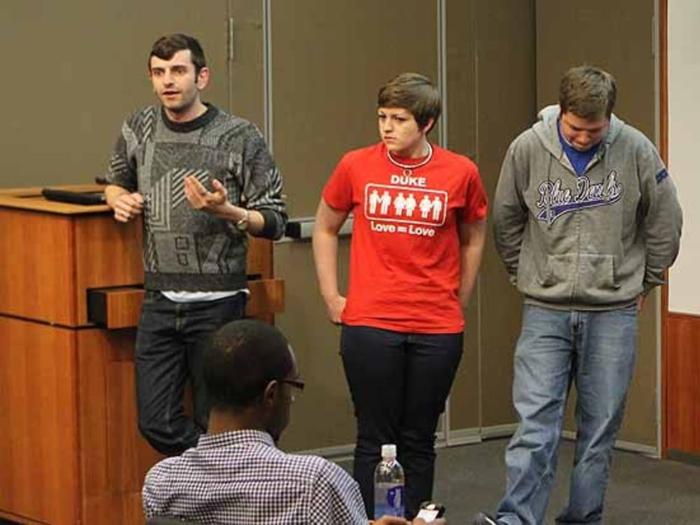 Junior Jacob Tobia, DSG senator for residential life (left), talks about expanding Duke's health care plan to include sexual reassignment surgery at the group's Wednesday meeting.
