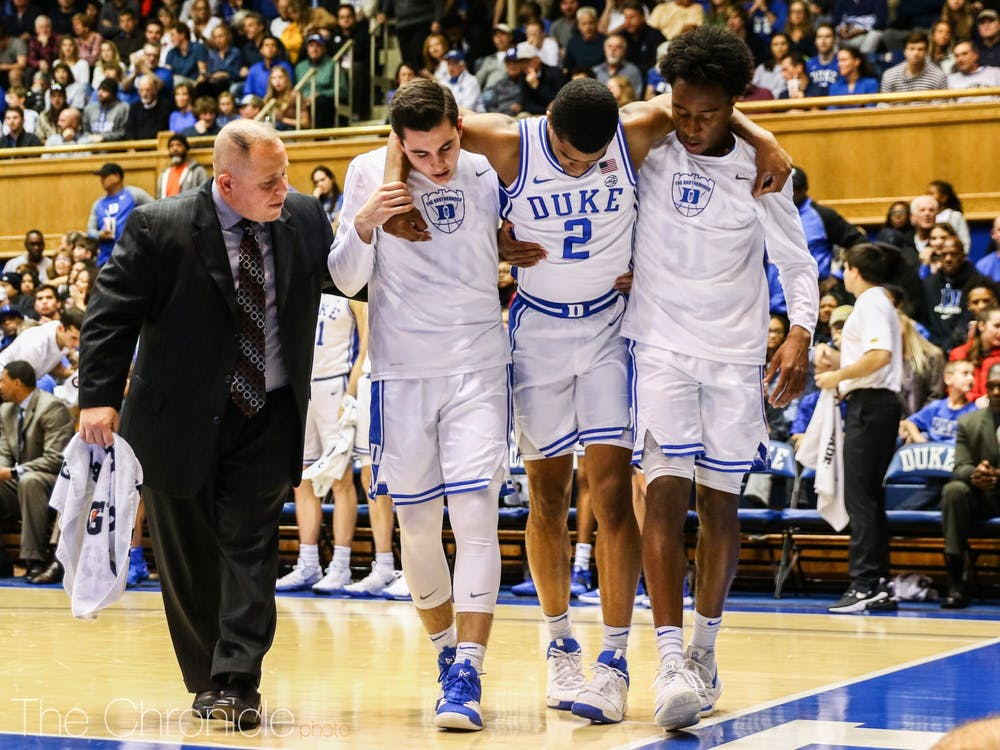 <p>Freshman guard Cassius Stanley is helped off of the court by Mike Buckmire and Michael Savarino. Stanley suffered an injury to his left knee early in the second half of Duke's win against Winthrop.</p>
