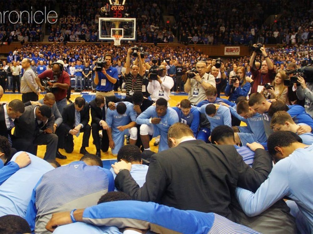 Duke and North Carolina kneeling at midcourt prior to their 2015 matchup, honoring legendary Tar Heel head coach Dean Smith less than two weeks after his death.