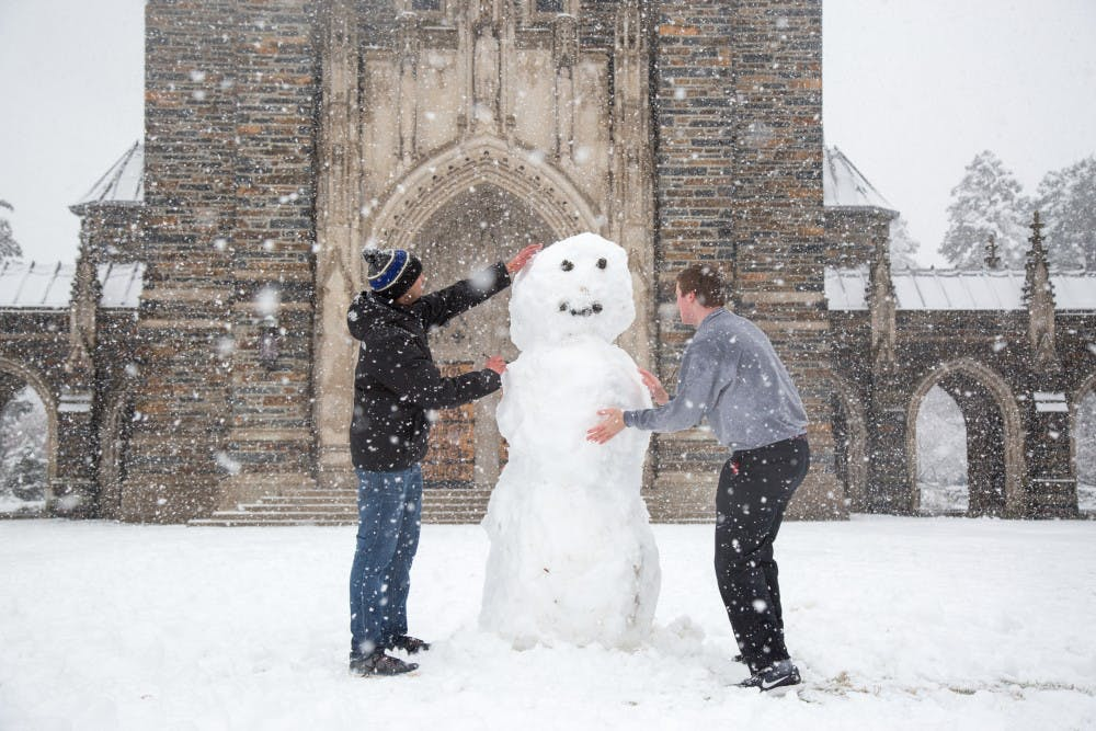 Sophomores Josh Young and Ameen Ahmad complete the finishing touches on their snowman in front the chapel.