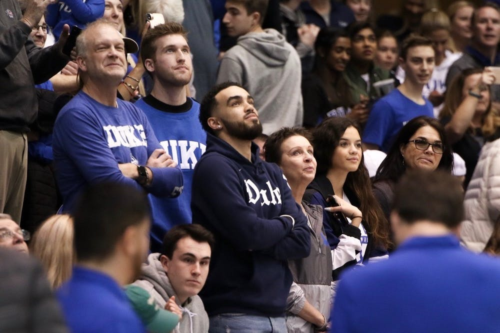 Tyus Jones, part of Duke's 2015 NCAA championship team and the older brother of Tre Jones, watches himself on Duke's pregame video.