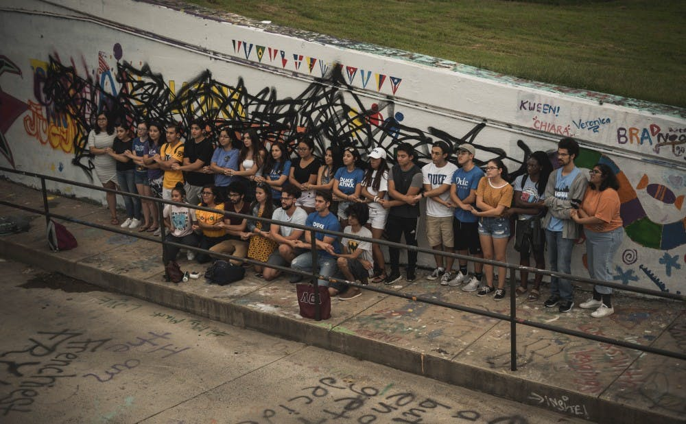 Students gathered at the East Campus bridge Saturday evening in response to a mural for Latinx Heritage Month being defaced earlier that day.