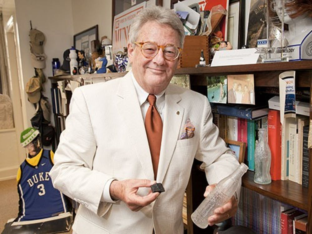 Tallman Trask photographed in his office with an old Coke bottle, Nehi bottle, and coal from the old steam plant.