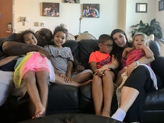 The Blackshear family sitting in their apartment in Trinity Dorm on East Campus. From left to right: Aiyana, John, Amoli, Andwele, Kimberly and Aza.