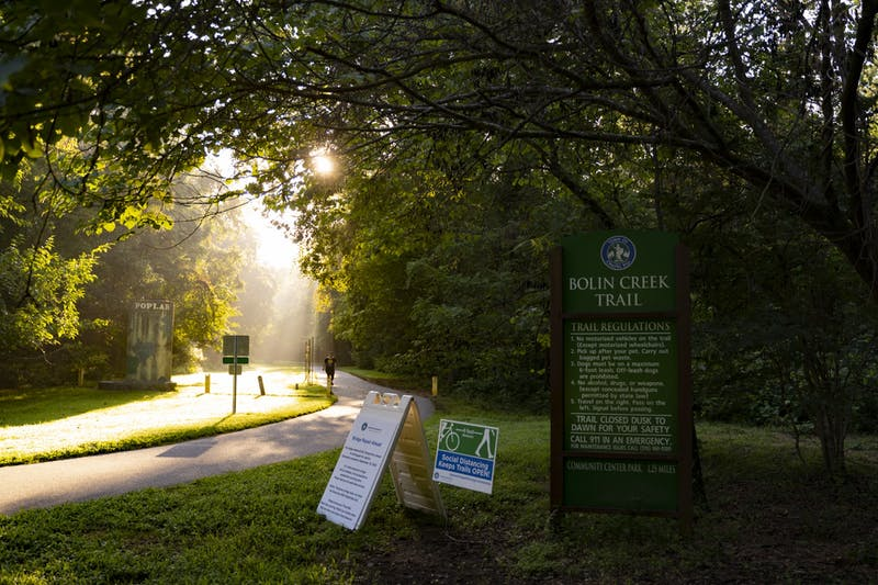 Early morning sunlight shines through the trees onto a pathway at Bolin Creek on Wednesday, Aug. 19, 2020.