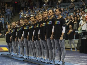 "The gymnastics team stands together wearing shirts with the saying ""#BeTrue"" in honor of the LBGTQ movement before their meet against Florida on Friday."