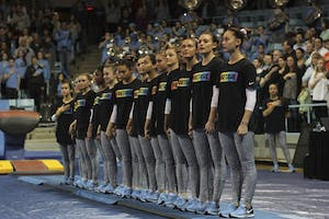 """The gymnastics team stands together wearing shirts with the saying """"#BeTrue"""" in honor of the LBGTQ movement before their meet against Florida on Friday."""