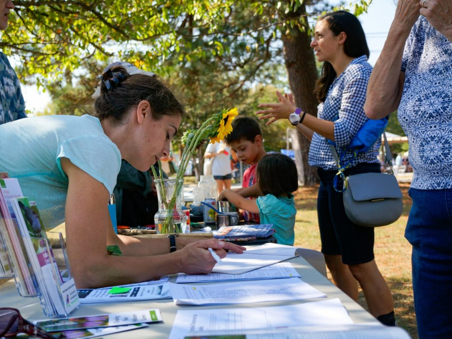 Carrboro resident Jeanette O'Conner, 37, writes her name down to receive more information regarding the Carrboro Community Climate Action Plan on Saturday, Sept. 21, 2019.