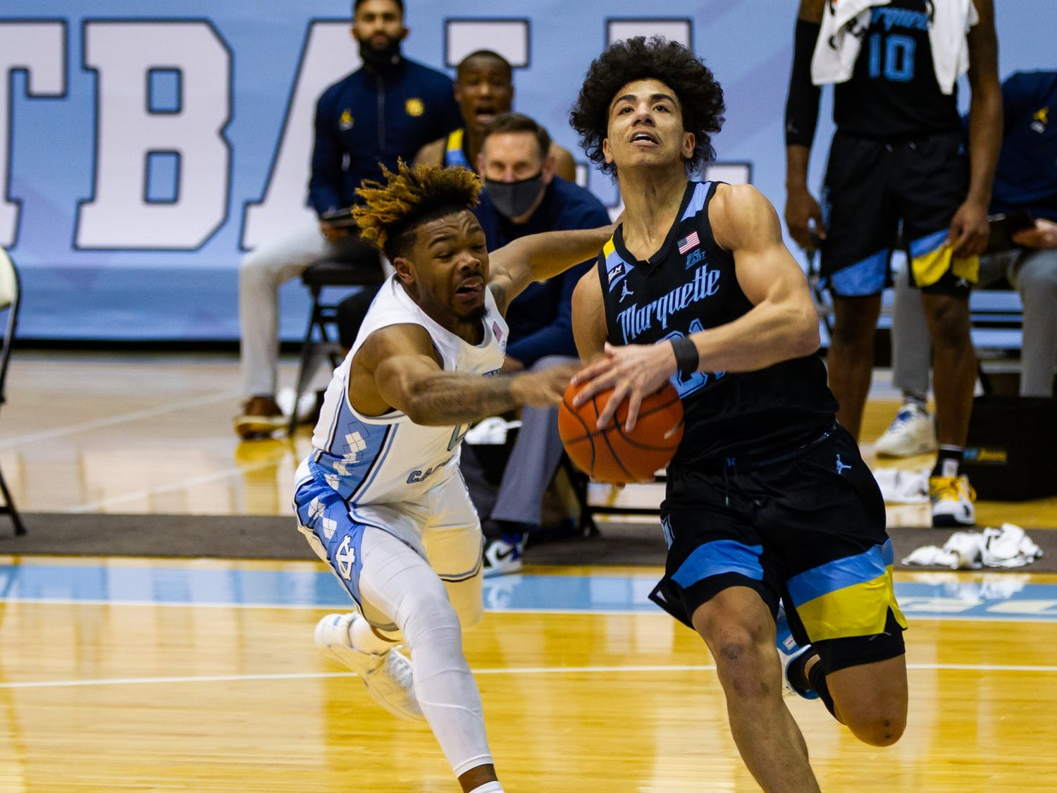 UNC redshirt first year guard Anthony Harris (0) attempts to knock the ball out of the hands of Marquette sophomore guard D.J. Carton (21) during a game in the Smith Center on Wednesday, Feb. 24, 202. UNC lost to Marquette 83-70.