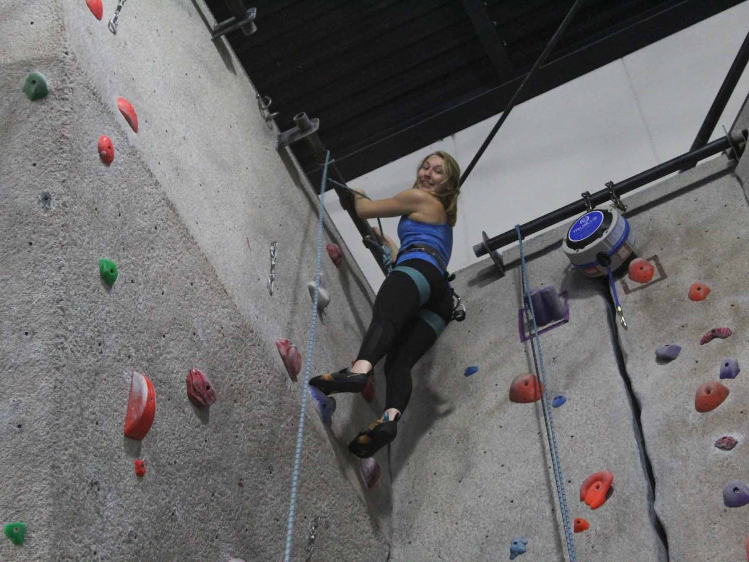 "Anna Baechtold, a first-year, art history major, reaches the top of the climbing wall during practice on Thursday, Feb. 27, 2020 at Fetzer Gym C. ""It's so literal and so easy to see your progress where in other sports, it's a bit more arbitrary"" she said."