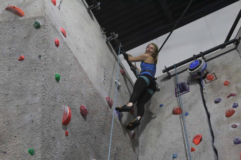 """Anna Baechtold, a first-year, art history major, reaches the top of the climbing wall during practice on Thursday, Feb. 27, 2020 at Fetzer Gym C. """"It's so literal and so easy to see your progress where in other sports, it's a bit more arbitrary"""" she said."""
