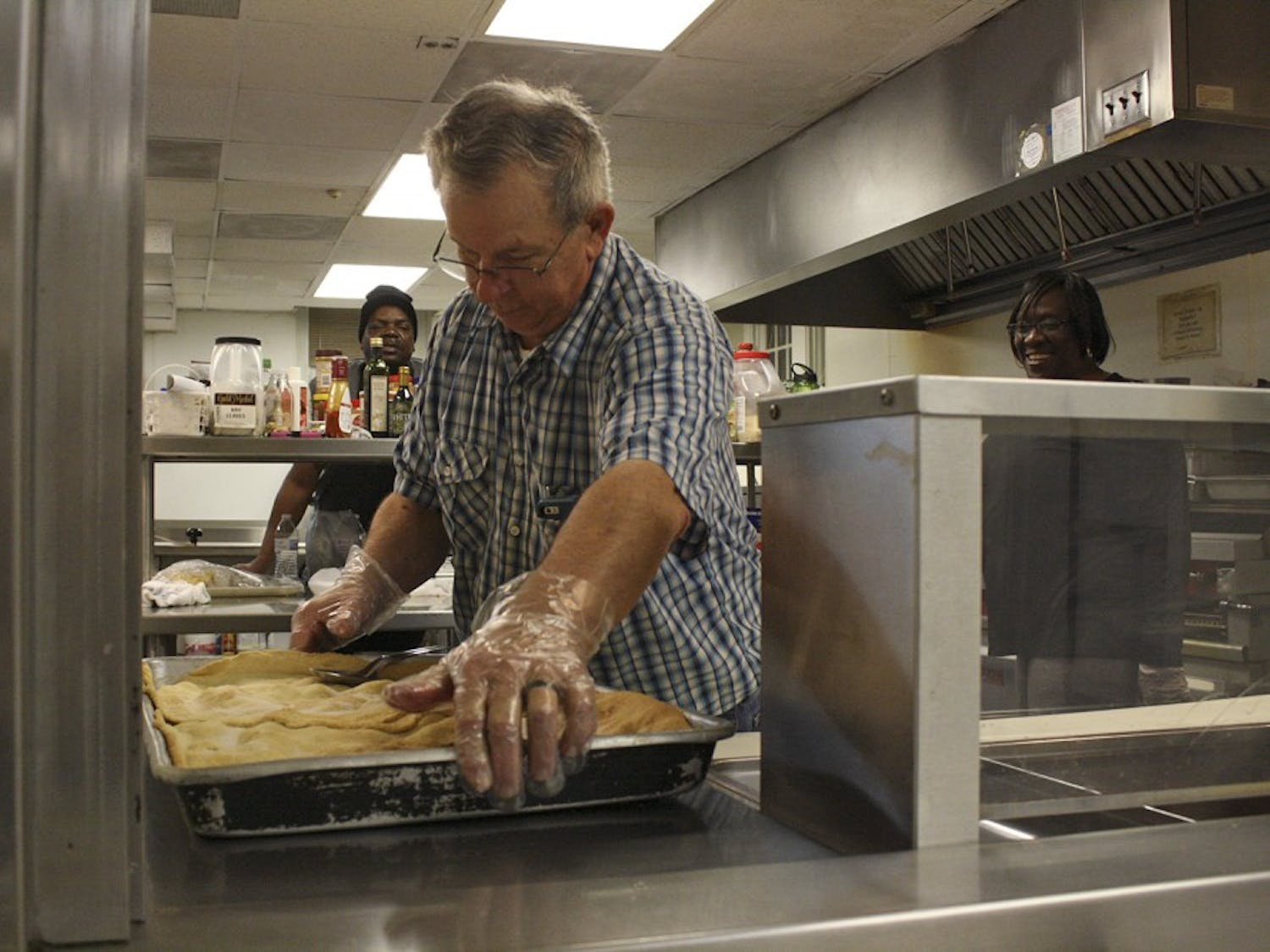 """Alvin Alston sets out some peach cobbler before """"Meet Me in the Kitchen"""", an event hosted by the IFC that works to feed those who need help in the Chapel Hill community. He has worked in the community kitchen for the past 12 years."""