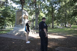 A campus police officer reads a sign that was removed from the Silent Sam statue on UNC's campus, on August 20, 2017.