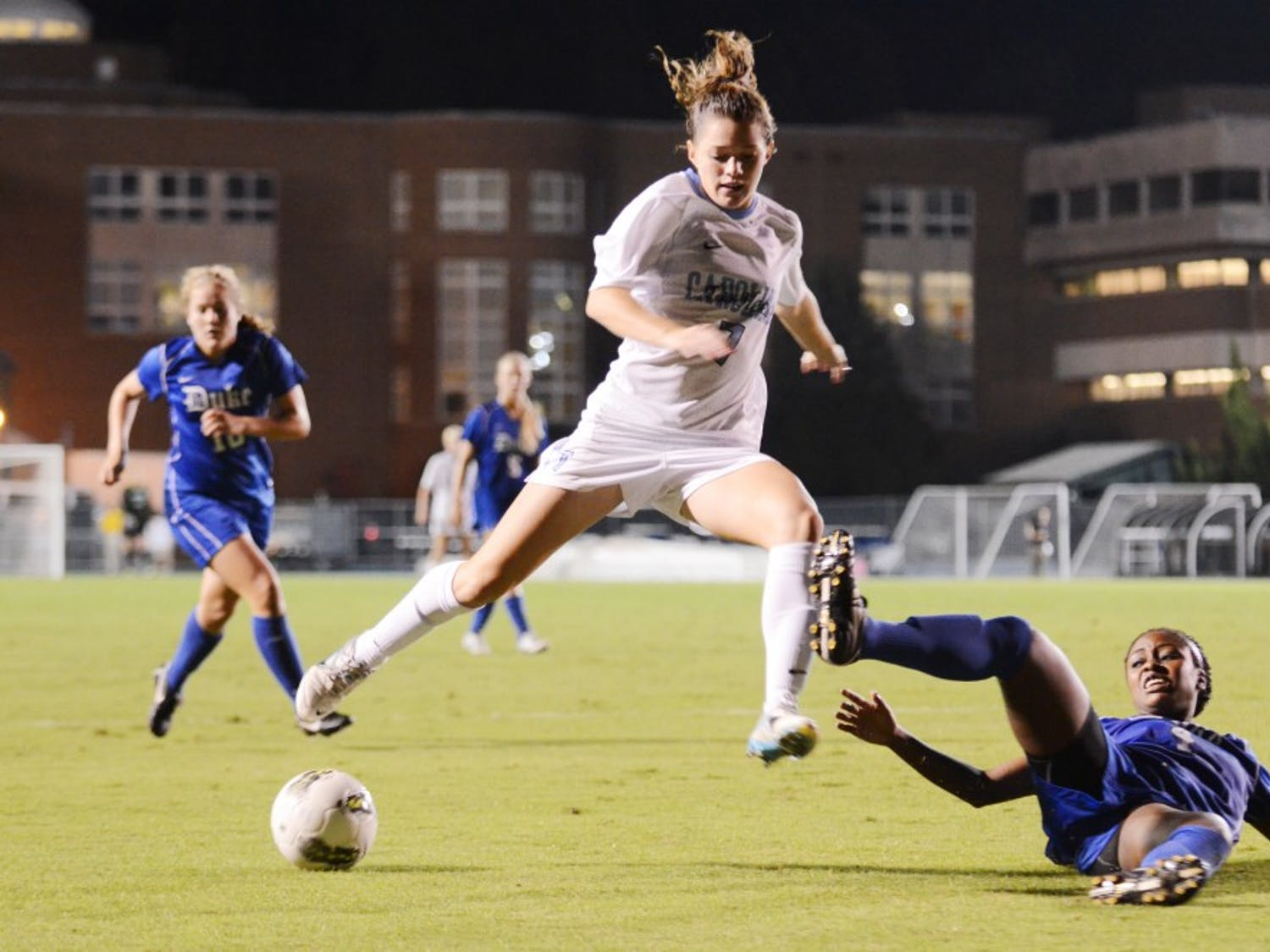 Kealia Ohai jumps over a fallen player and dribbles down Fetzer Field. Ohai scored the winning goal against the Blue Devils in the 88th minute.