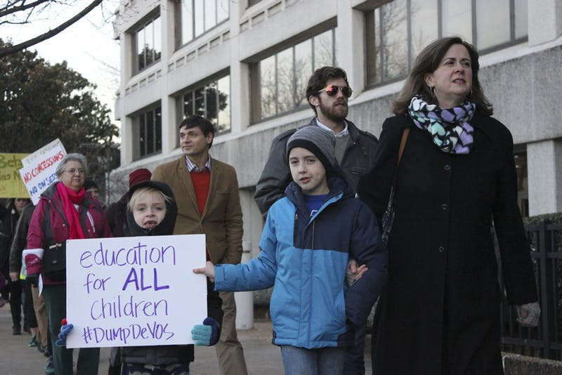"""From left: Colin, Christopher, and Marty Long protest the nomination of Betsy DeVos for United States' Secretary of Education""""We are here because DeVos is a terrible idea for Secretary of Education."""" """"As a mother, my child is not receiving the best education, and not all children are receiving the best education."""""""