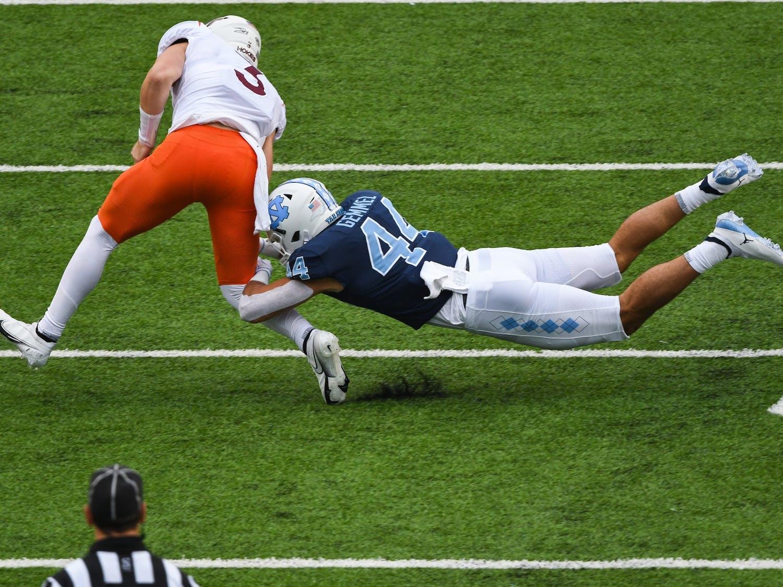 UNC junior linebacker Jeremiah Gemmel (44) tackles Virginia Tech redshirt junior quarterback  Braxton Burmeister (3) during a game in Kenan Memorial Stadium on Saturday, Oct. 10, 2020. UNC beat Virginia Tech 56-45.