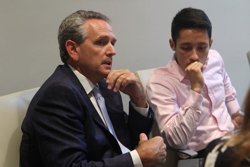 Bubba Cunningham (left), UNC Athletic Director, contributes to discussion at a 2016 meeting of the Faculty Athletics Committee (FAC) while Ezra Baeli-Wang, a student athlete advisory council representative, listens intently.