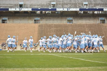 The UNC men's lacrosse team celebrates after a 12-11 overtime win against Lehigh on Feb. 17 in Kenan Stadium.