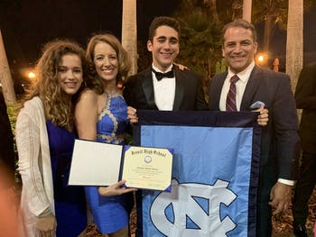 Alex Cáceres (second from right) is a first-year at UNC continuing a Tar Heel tradition — his father, Pablo (right) graduated in 1989.