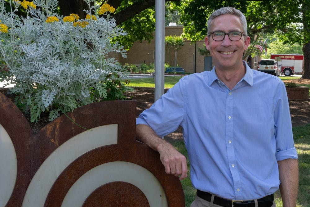 <p>Damon Seils, Carrboro council member, poses beside the Carrboro Town Hall sign on Tuesday, June 8, 2021. Seils announced he is running for Mayor of Carrboro.</p>