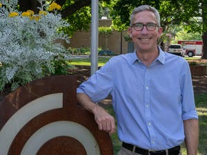 Damon Seils, Carrboro council member, poses beside the Carrboro Town Hall sign on Tuesday, June 8, 2021. Seils announced he is running for Mayor of Carrboro.
