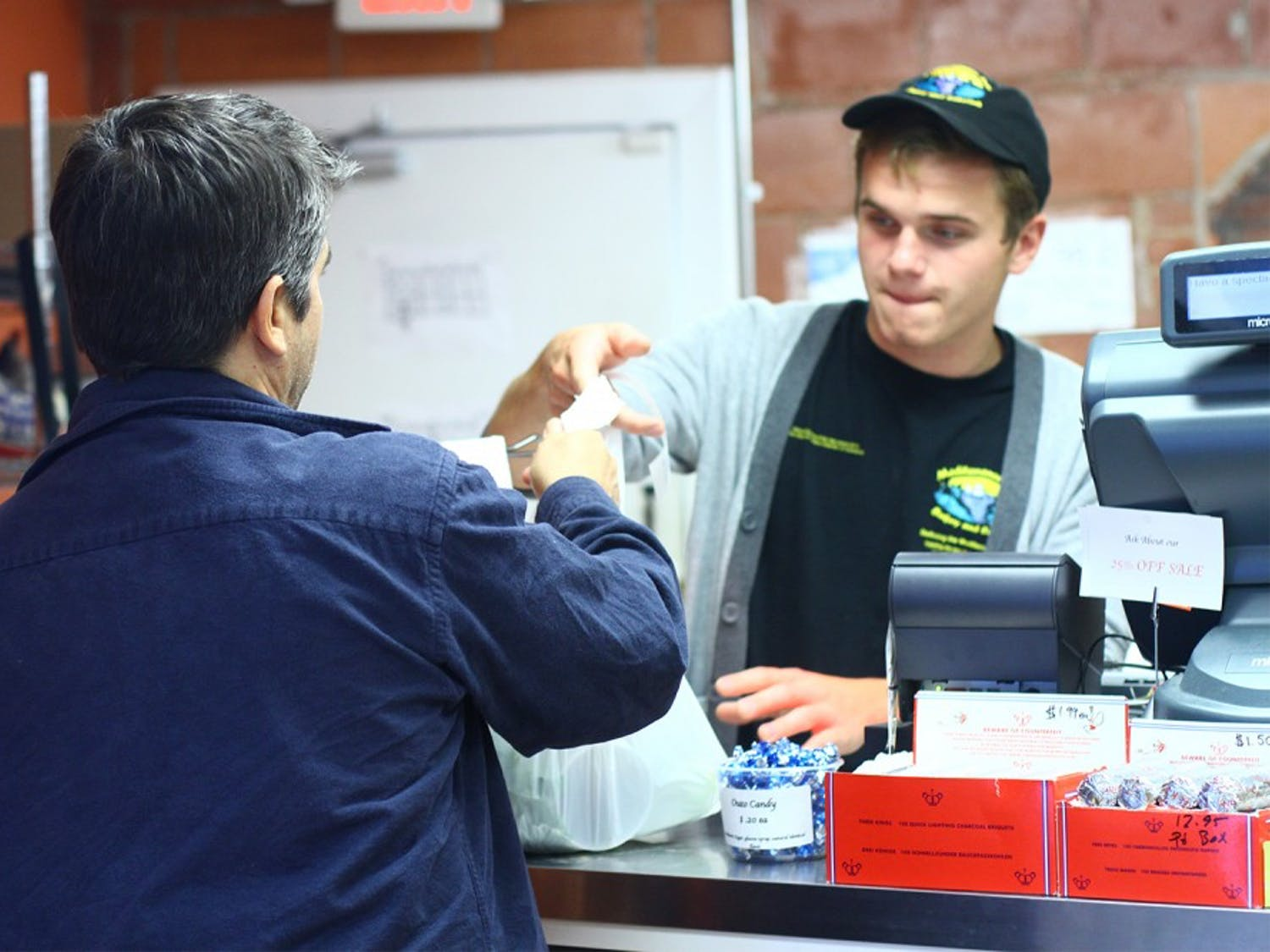 Steve Richichi of Chapel Hill, picks up a few things at the Mediterranean Deli Market on Monday evening. He says he enjoys the fresh produce and the prices are great too. Employee, Lukas Zdanavicius.