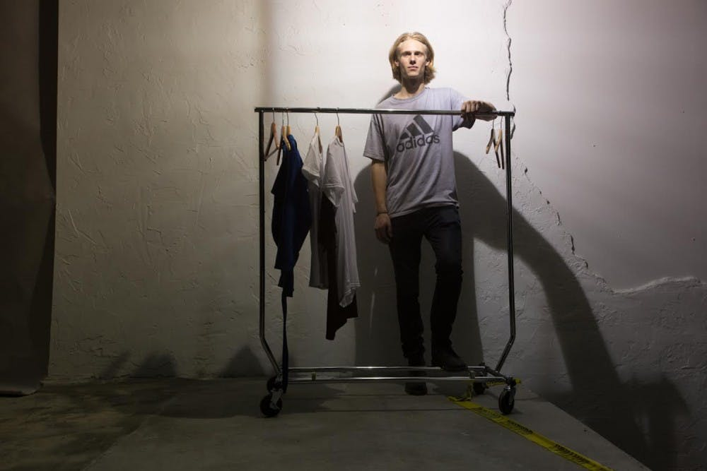 <p>James Creissen, a sophomore business major, poses in front of a rack of clothes he designed. Creissen held a fashion show on East Rosemary Street Thursday night.</p>
