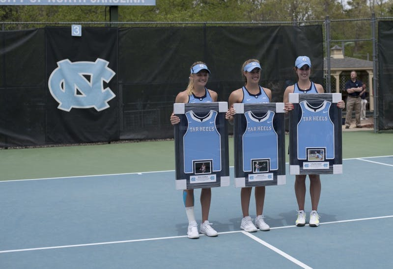 From left to right, seniors Marika Akkerman, Maggie Kane, and Cassandra Vazquez pose with their framed uniforms on Senior Sunday against Pittsburgh on April 22 at the Cone-Kenfield Tennis Center.