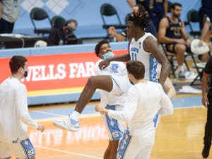 UNC first year forward Day'Ron Sharpe (11) celebrates with KJ Smith and Walker Miller following Carolina's 66-65 win over Notre Dame at the Dean E. Smith Center, January 2nd, 2021.