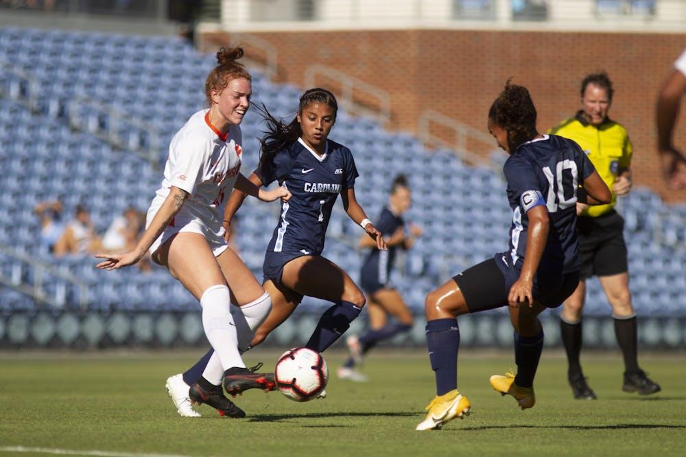 <p>UNC first year midfielder Sam Meza (1) and junior midfielder Rachel Jones (10) fight for the ball with Clemson sophomore midfielder Hal Hershfelt (15) during a game at Dorrance Field on Thursday, Oct. 1, 2020. UNC beat Clemson 2-0.&nbsp;</p>