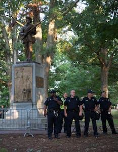 Police officers gather around Silent Sam.