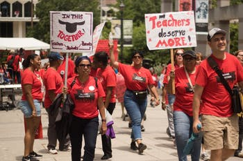 Educators carry signs through Bicentennial Plaza during the rally for education on May 16 in Raleigh.