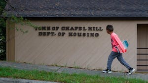 A young boy with a skateboard walks past the Chapel Hill Department of Housing in the Northside neighborhood of Chapel Hill on Sunday, Oct. 25, 2020.