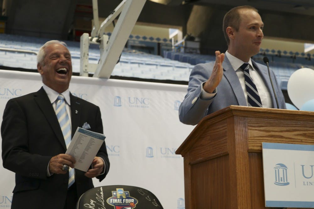 <p>UNC play-by-play announcer Jones Angell and men's basketball head coach Roy Williams address the crowd at Williams' Fast Break Against Cancer event in the Smith Center on Monday, Oct. 2, 2017.</p>