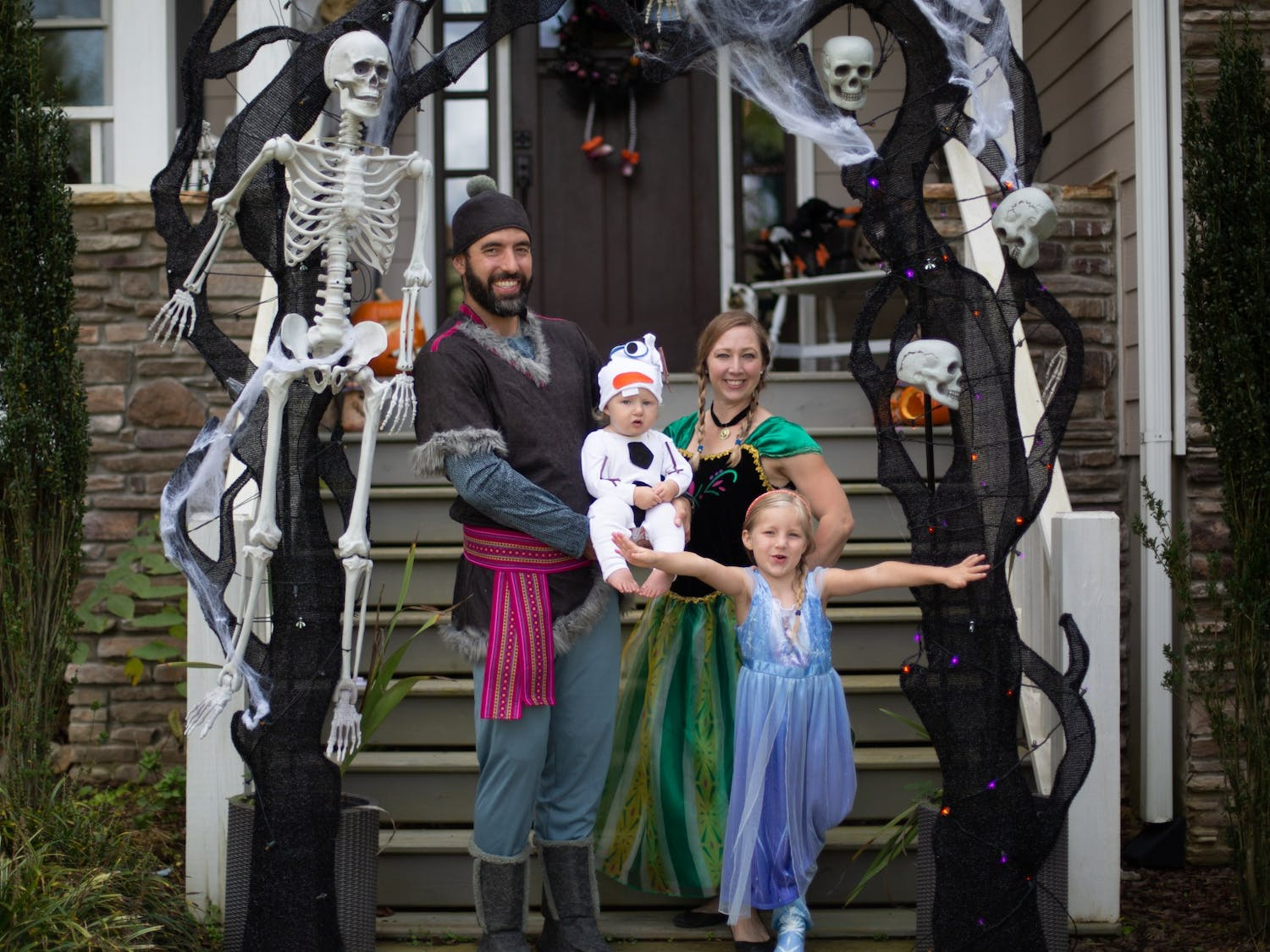From left: Chad, Liam, Kelly, and Evelyn Edwards pose for a portrait in their front yard. The Edwards family chose to dress as characters from Disney's Frozen: Chad is Kristoff, Liam is Olaf, Kelly is Anna, and Evelyn is Elsa.