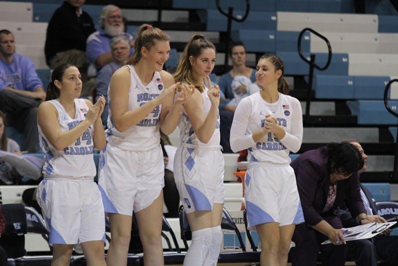 Teammates Liz Roberts (14), Naomi Van Nes (34), Emily Sullivan (11) and Olivia Smith (15) celebrate on the bench against Radford.