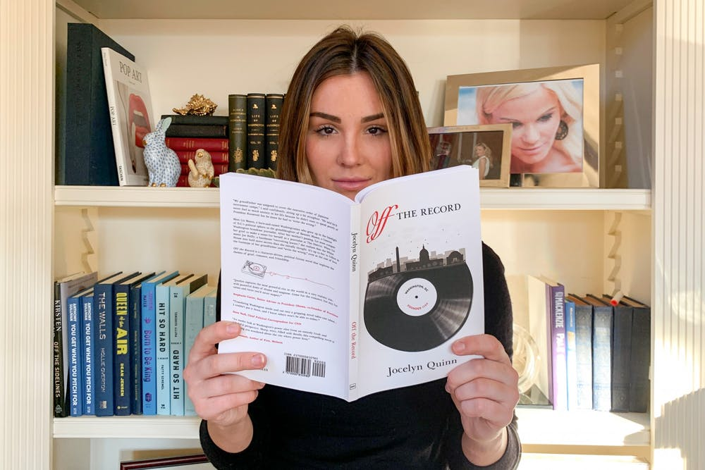 """Jocelyn Quinn poses for a virtual portrait with her new novel, """"Off the Record,"""" at her family home in Washington D.C. on Wednesday, Jan. 20, 2020. Pictured on the bookshelf behind her is her mother, Susanna Quinn, who she cites as the inspiration for her story's main character, Liz Mason."""