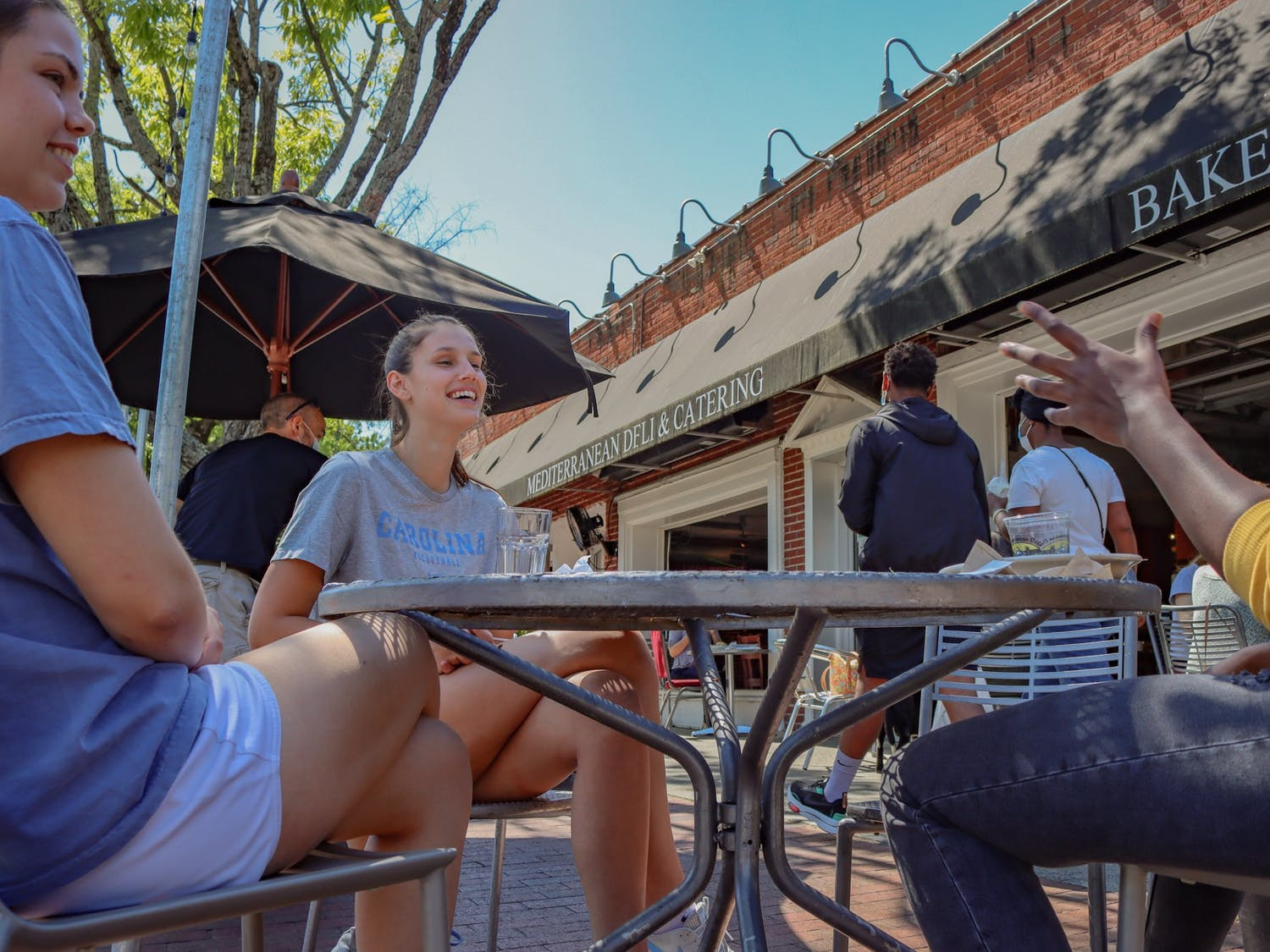 UNC junior Erin Boone, seinor Artistea Tontai, and Isiuwa Oghagbon chat after enjoying an outdoor meal at Mediterranenan Deli on Franklin Street on Monday, April 26.