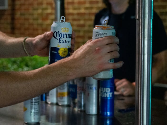 DTH Photo Illustration. A vendor sells two alcoholic beverages to a customer during a UNC football game at Kenan Stadium on Sept. 18, 2021.