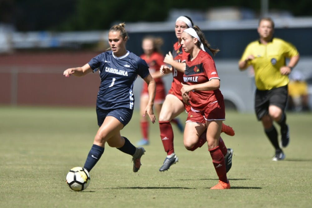 <p>Junior forward Madison Schultz outruns Louisville defenders during a 5-1 win over the Cardinals on Sept. 29, 2018.</p>