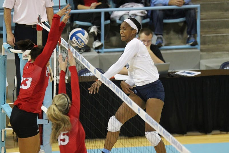 Senior opposite hitter Chaniel Nelson spikes the ball over NC State players and helped contribute to the Heels' .351 team hitting percentage.