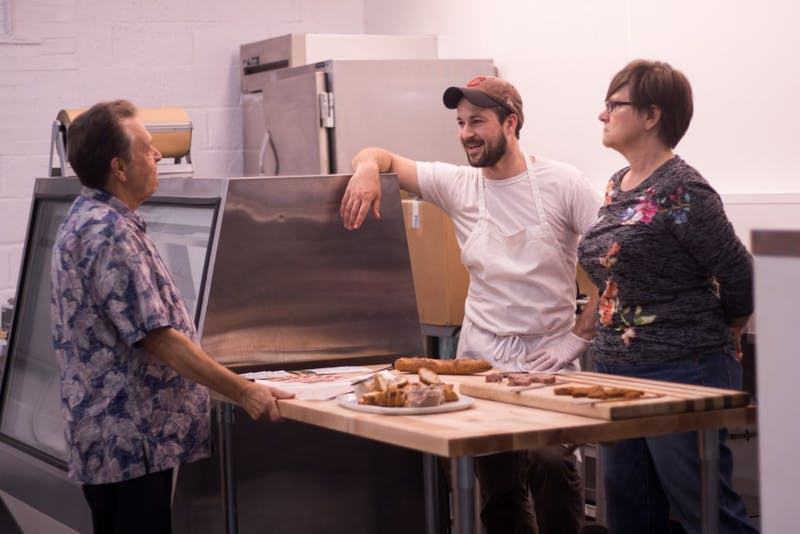 Left Bank is a whole animal butcher shop in Saxapahaw, NC. Ross Flynn, butcher and owner, and Judy Shertzer, the soon-to-be manager of the Blue Dogwood location, talk to a guest about their products.