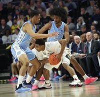 Sophomore forward Garrison Brooks (15) and first-year guard Coby White (2) swarm a Wake Forest defender in No. 8 UNC's 95-57 win over Wake Forest on Saturday, Feb. 16, 2019 at Lawrence Joel Veterans Memorial Coliseum.
