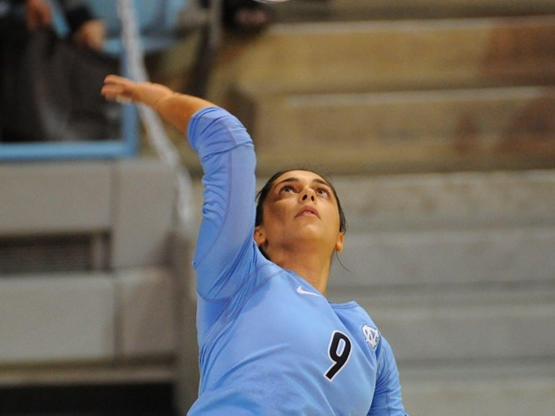 UNC libero Ece Taner (9) serves the ball.