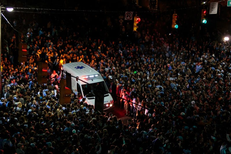 An ambulance is surrounded by thousands of fans that rushed Franklin Street after the North Carolina men's basketball team defeated Duke Saturday night.