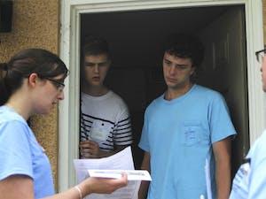Good Neighbor Initiative volunteers, Cassandra Bennet (far left) and C.J. Click (far right) speak with UNC students Jakob Nielsen (left) and Nataniel Lelental (right).